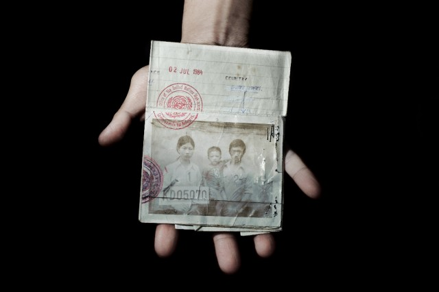 Sonny Vaahn, 25, holds the refugee identification card of his family members, which was given upon initial entry into a refugee camp along the Thai-Cambodian border following the end of the Killing Fields in Cambodia. Bronx, New York, Sept. 2011.